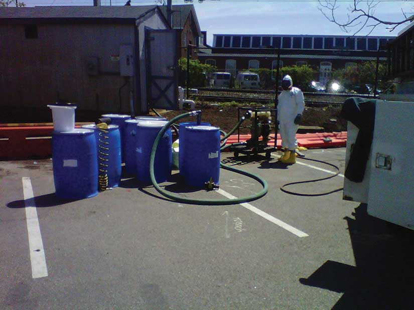 Blue waste barrels with person in Hazmat suit