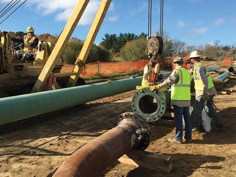 Workers standing by big pipes